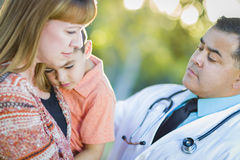 Sick Mixed Race Boy, Mother and Hispanic Doctor Outdoors Stock Images