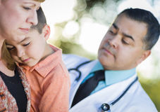Sick Mixed Race Boy and Mother with Hispanic Doctor Outdoors Royalty Free Stock Photos