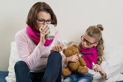 Sick mother and daughter. A women with a runny nose, she sneezes, using a handkerchief, drinking hot tea, medicine Royalty Free Stock Photo