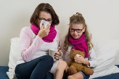 Sick mother and daughter. A women with a runny nose, she sneezes, using a handkerchief, drinking hot tea, medicine Royalty Free Stock Image