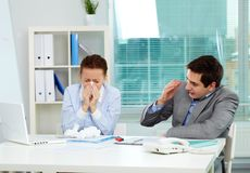 Sick in office. Image of businesswoman sneezing while her partner looking at her unsurely in office Stock Photography