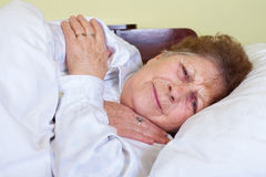 Sick old lady in bed Stock Photo