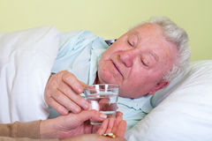 Sick old man in bed, receiving his pills Royalty Free Stock Photo