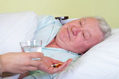 Sick old man in bed, receiving his pills Royalty Free Stock Photography