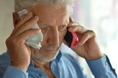 Sick old man calling doctor Royalty Free Stock Image
