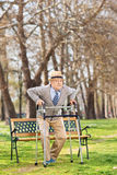 Sick old man standing up with walker in park Royalty Free Stock Images