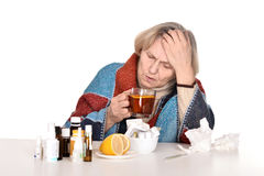 Sick old woman drinks tea. Portrait of an elderly sick woman over a white background stock image
