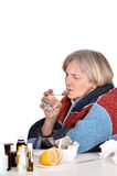 Sick old woman drinks water. Portrait of an elderly sick woman drinks water over a white background Stock Photography
