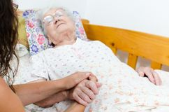 Sick old woman. Old woman sick, hand being hold by her caring daughter Stock Images