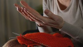 Sick old woman looking at shaking hands, unable to knit, old age difficulties