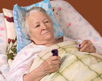 Sick old woman lying at bed. Sick senior woman lying at bed Stock Images