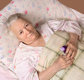 Sick old woman lying at bed Royalty Free Stock Image