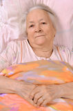Sick old woman. Lying at bed Royalty Free Stock Photography