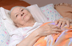 Sick old woman. Lying at bed Royalty Free Stock Images
