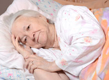 Sick old woman. Lying at bed Stock Image