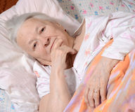 Sick old woman. Lying at bed Royalty Free Stock Photos