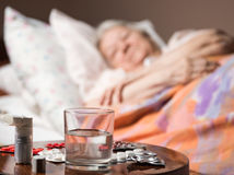 Sick old woman lying at bed bed. With focus on medicine and glass of water in foreground Royalty Free Stock Photography