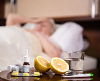 Sick old woman lying at bed. Flu.  Headache. Virus .Medicines on a foreground Stock Image