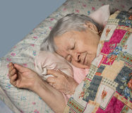Sick old woman. Lying in bed at hoke Stock Photo