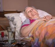 Sick old woman lying in bed at home Royalty Free Stock Photography