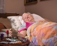 Sick old woman lying in bed at home Royalty Free Stock Photos