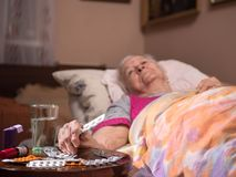 Sick old woman lying in bed at home. Healthcare, medical concept. Sick old woman lying in bed at home. Focus on medicine and glass of water on foreground Stock Image