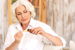 Sick old woman preparing medication against cough Stock Images