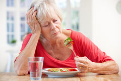 Sick older woman trying to eat Stock Photo