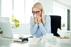 Sick and overworked businesswoman in the office, blowing her nos stock photos