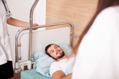 Sick Patient in hospital room next to nurses Stock Image