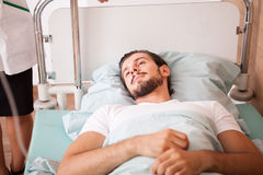 Sick Patient in hospital room next to nurses stock images