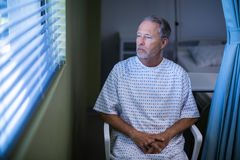 Sick patient sitting on chair and looking through window blinds. In hospital Stock Photo