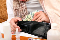 Sick Person checks the Wallet. Sick Person checking the Wallet with the Pills on foreground closeup Royalty Free Stock Photo