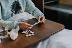 Sick person taking medicine. Cropped shot of sick person holding thermometer above table with pills Royalty Free Stock Image