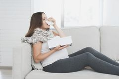 Sick pregnant woman sitting at home on the couch. She flies herself into a paper napkin. The woman has a cold Royalty Free Stock Images