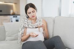 Sick pregnant woman sitting at home on the couch. She`s getting ready to drink a pill. Stock Photos