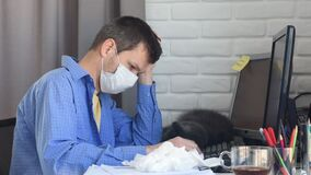 A sick quarantined medical mask employee works on a computer