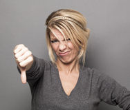 Sick 20s girl expressing repulsion with thumb down and grimace Royalty Free Stock Photo