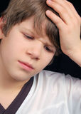 Sick and Sad Boy. This boy is either sad or sick.  Does he have a headache or is he simply upset?  What is bothering him?  You decide Royalty Free Stock Image