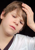 Sick and Sad Boy. This boy is either sad or sick.  Does he have a headache or is he simply upset?  What is bothering him?  You decide Royalty Free Stock Photos