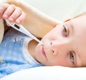 Sick and sad kid in bed Stock Image