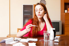 Sick sad red-haired woman looks by thermometer at home Royalty Free Stock Image