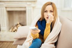 Sick sad woman sitting on the couch with remote control. Sick leave. Beautiful cheerless young dark-eyed woman having runny nose and feeling unwell and sitting Stock Photos