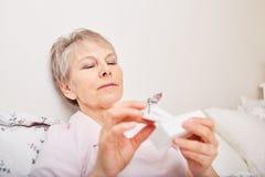 Sick senior citizen holding pill dispenser. With medication Royalty Free Stock Image