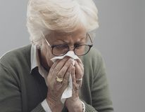 Sick senior lady blowing nose royalty free stock photos