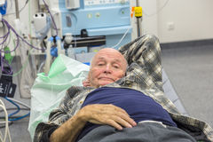 Sick senior lying in an emergency room. Sick senior man lying in an emergency room in a new hospital in Usingen, Germany stock image