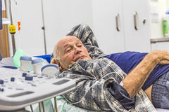 Sick senior lying in a hospital bed Royalty Free Stock Images