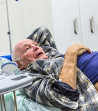 Sick senior lying in a hospital bed Stock Image