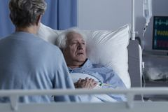 Sick senior man with alzheimer. Worried wife visiting sick senior men with alzheimer connected to a drip in health center Royalty Free Stock Image