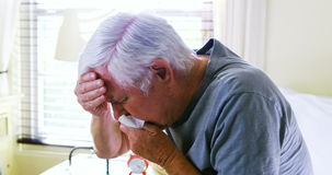 Sick senior man coughing in bedroom